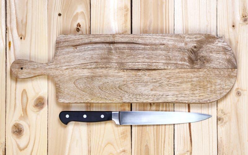 Τέμνων πίνακας με το μαχαίρι στον ξύλινο πίνακα Τοπ όψη στοκ φωτογραφία με δικαίωμα ελεύθερης χρήσης