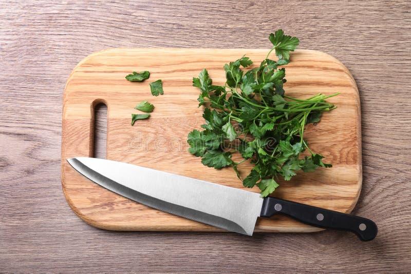 Τέμνων πίνακας με το μαχαίρι του αρχιμάγειρα και φρέσκος μαϊντανός στον ξύλινο πίνακα στοκ εικόνες