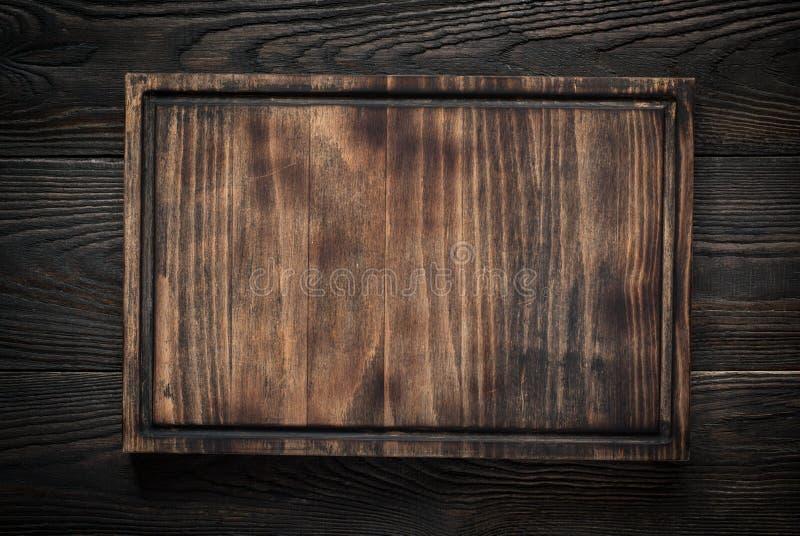 Τέμνων πίνακας στο σκοτεινό ξύλινο πίνακα στοκ φωτογραφία με δικαίωμα ελεύθερης χρήσης