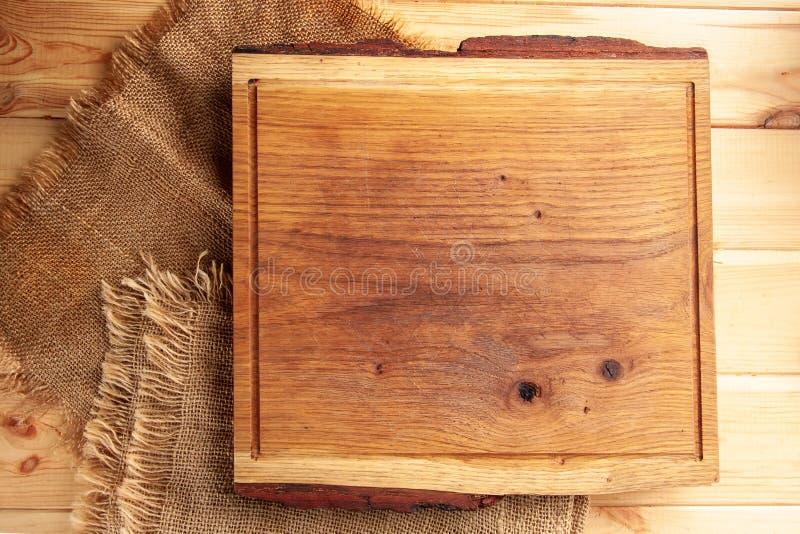 Τέμνων πίνακας sackcloth στον ξύλινο πίνακα στοκ εικόνες