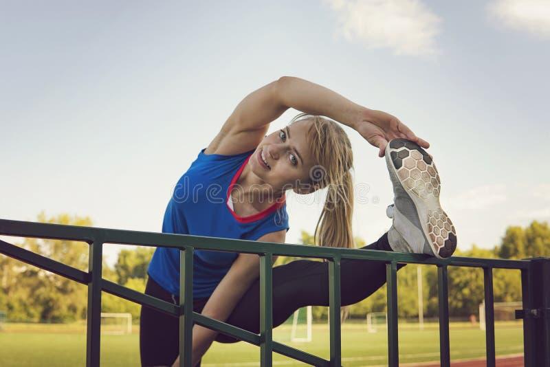 Τέντωμα γυναικών αθλητικής ικανότητας στο στάδιο Όπλα τεντώματος αθλητικών ξανθά κοριτσιών στον αθλητικό τρέχοντας χώρο με πολλές στοκ φωτογραφίες με δικαίωμα ελεύθερης χρήσης