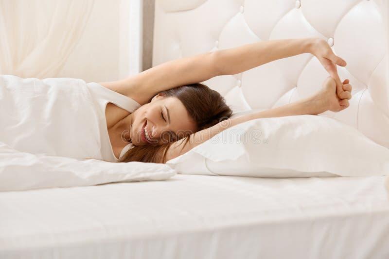 Τέντωμα γυναικών στο κρεβάτι της Ένα κορίτσι που ξυπνά το πρωί στοκ εικόνα