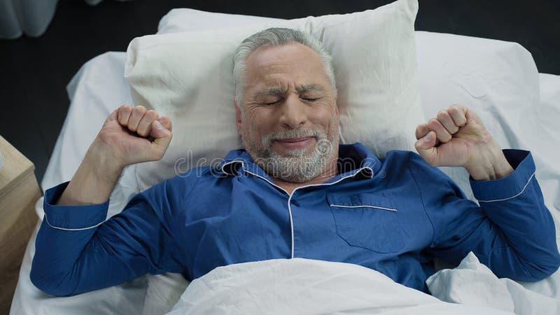 Τέντωμα συνταξιούχων στο κρεβάτι του μετά από να ξυπνήσει το πρωί, υγιής ύπνος στοκ εικόνα