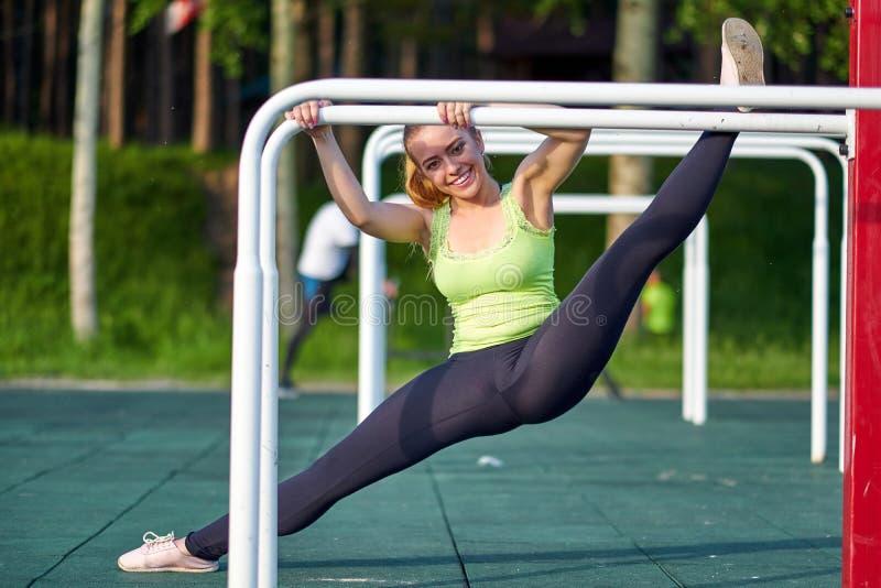 Τέντωμα danser ή gymnast τραίνα κατάρτισης γυναικών στους ανώμαλους φραγμούς στο χώρο αθλήσεων workout Καλό τέντωμα, σπάγγος στοκ εικόνα με δικαίωμα ελεύθερης χρήσης