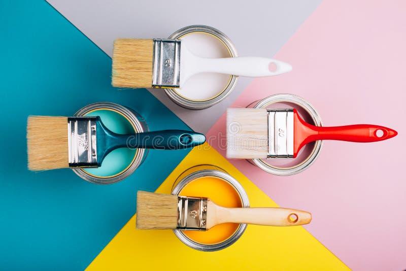 Τέσσερα ανοικτά δοχεία του χρώματος με τις βούρτσες σε τους στο φωτεινό υπόβαθρο συμμετρίας στοκ φωτογραφία