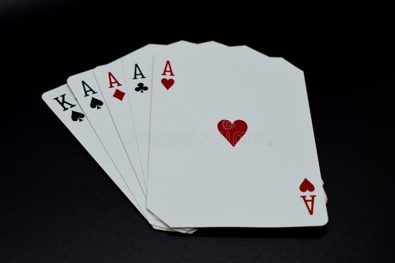 Τέσσερα από ένα είδος άσσων στο αυθεντικό παιχνίδι καρτών χαρτοπαικτικών λεσχών πόκερ σε ένα μαύρο υπόβαθρο στοκ εικόνες