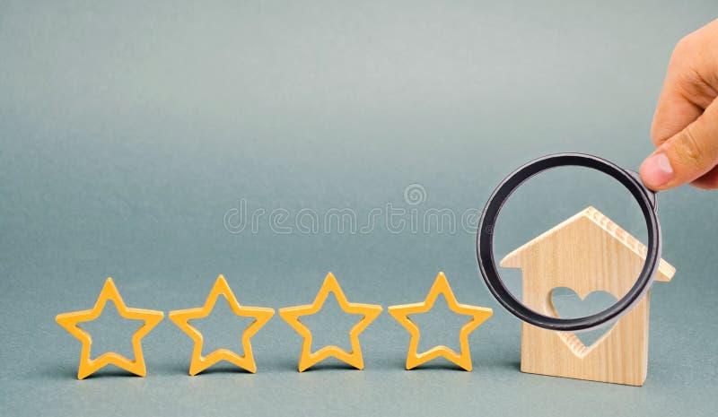 Τέσσερα αστέρια και ένα ξύλινο σπίτι σε ένα γκρίζο υπόβαθρο   Ανατροφοδότηση Καλή αξιολόγηση του κριτικού Εκτίμηση ξενοδοχείων Πο στοκ φωτογραφία με δικαίωμα ελεύθερης χρήσης