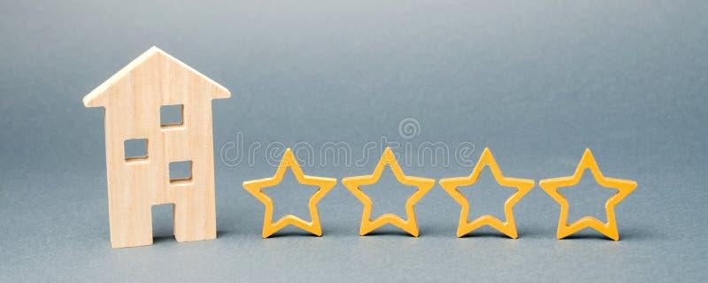 Τέσσερα αστέρια και ένα ξύλινο σπίτι σε ένα γκρίζο υπόβαθρο   Ανατροφοδότηση Καλή αξιολόγηση του κριτικού Εκτίμηση ξενοδοχείων Πο στοκ εικόνα