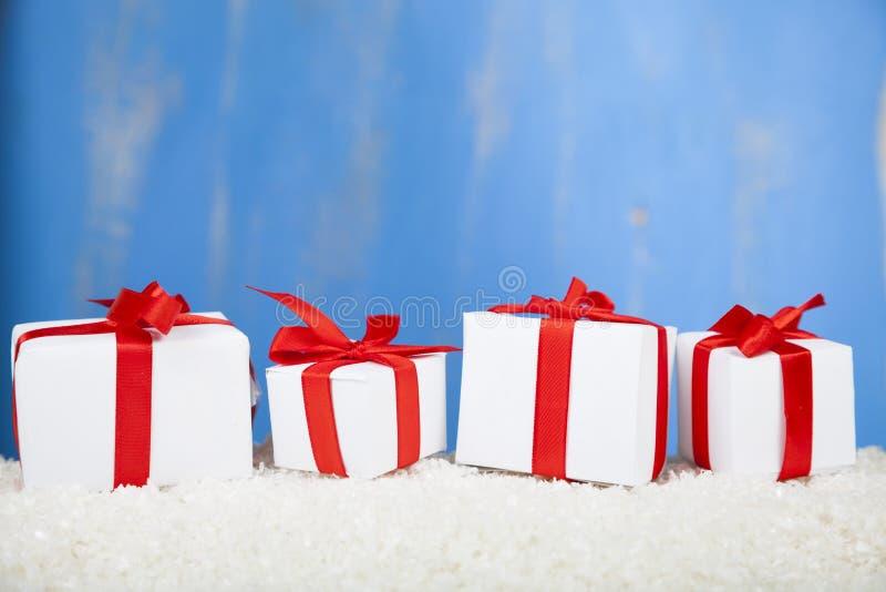 Τέσσερα δώρα με τα κόκκινα τόξα στο χιόνι στοκ εικόνες