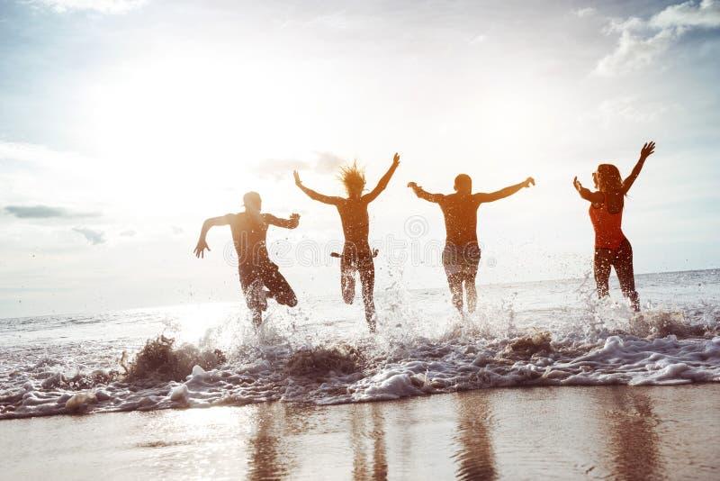 Τέσσερα ευτυχή τρεξίματα φίλων στην παραλία ηλιοβασιλέματος στοκ εικόνες