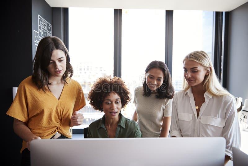 Τέσσερα θηλυκά creatives που λειτουργούν γύρω από ένα όργανο ελέγχου υπολογιστών σε ένα γραφείο, μπροστινή άποψη, κλείνουν επάνω στοκ φωτογραφία με δικαίωμα ελεύθερης χρήσης