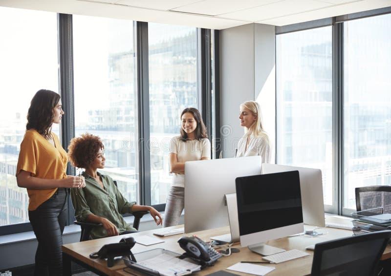 Τέσσερα θηλυκό συνάδελφοι στη συζήτηση σε ένα γραφείο σε ένα δημιουργικό γραφείο, που εξετάζει το ένα το άλλο στοκ φωτογραφίες με δικαίωμα ελεύθερης χρήσης