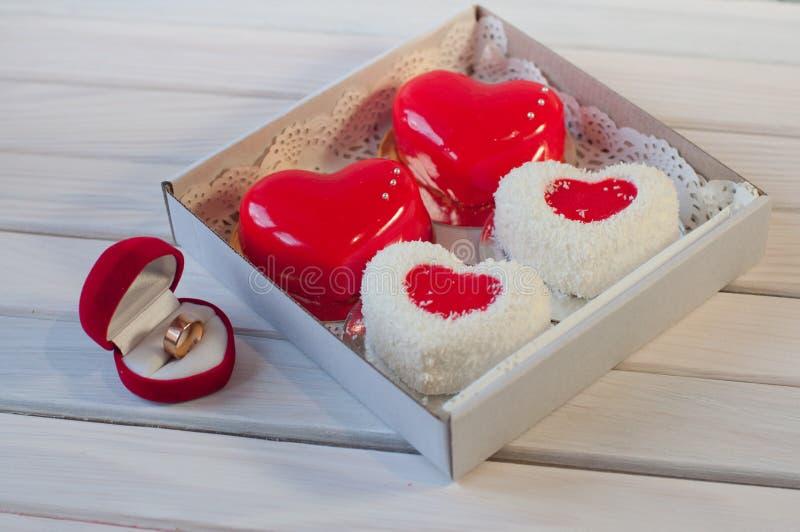 Τέσσερα διαμορφωμένα καρδιά κέικ στο κιβώτιο και το γαμήλιο δαχτυλίδι στον πίνακα στοκ εικόνα με δικαίωμα ελεύθερης χρήσης