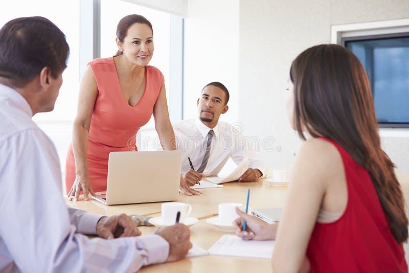 Τέσσερα ισπανικό Businesspeople που διοργανώνουν τη συνεδρίαση στην αίθουσα συνεδριάσεων στοκ εικόνα
