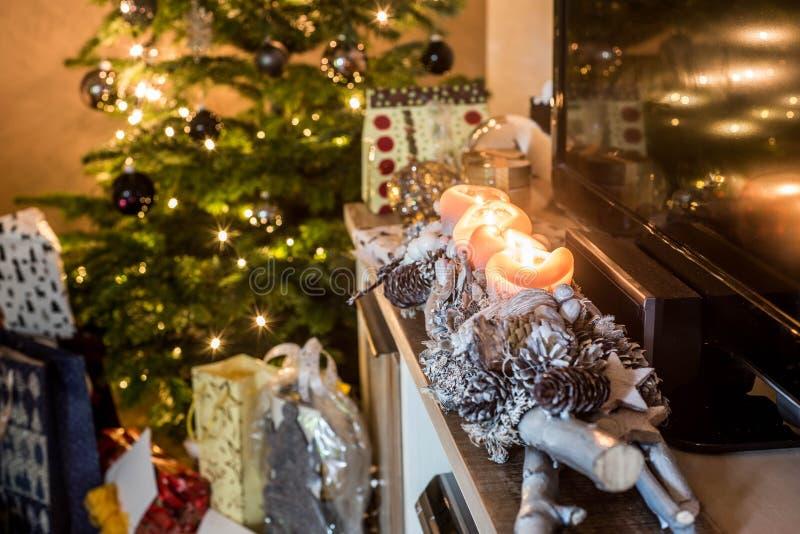 Τέσσερα καίγοντας κεριά εμφάνισης, όμορφα διακοσμημένα φω'τα οργάνωσης στο χριστουγεννιάτικο δέντρο υποβάθρου με τα δώρα στοκ εικόνα