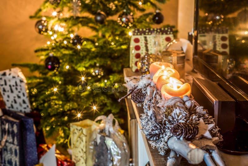 Τέσσερα καίγοντας κεριά εμφάνισης, όμορφα διακοσμημένα φω'τα οργάνωσης στο χριστουγεννιάτικο δέντρο υποβάθρου με τα δώρα στοκ εικόνες