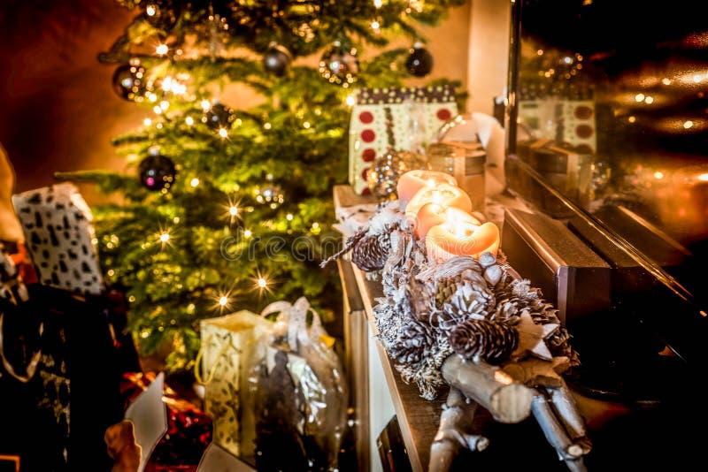 Τέσσερα καίγοντας κεριά εμφάνισης, όμορφα διακοσμημένα φω'τα οργάνωσης στο χριστουγεννιάτικο δέντρο υποβάθρου με τα δώρα στοκ φωτογραφία με δικαίωμα ελεύθερης χρήσης