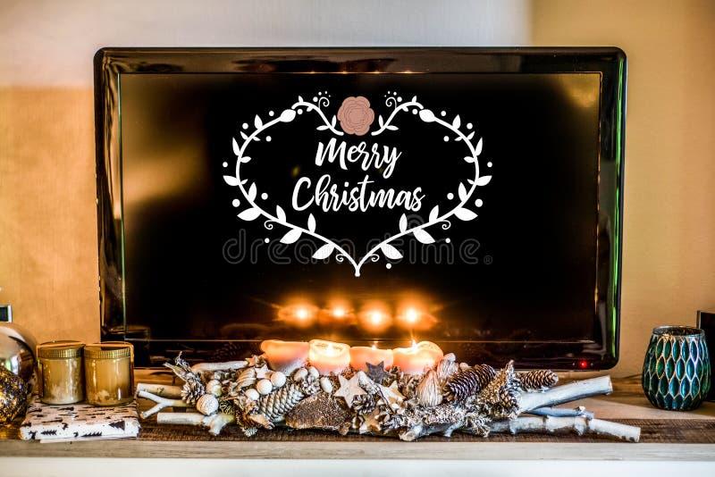 Τέσσερα καίγοντας κεριά εμφάνισης, όμορφη διακοσμημένη ελαφριά TV οργάνωσης στο υπόβαθρο textspace που λέει τη Χαρούμενα Χριστούγ στοκ εικόνες