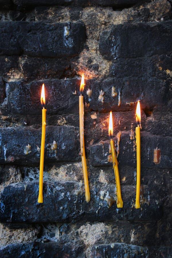Τέσσερα καίγοντας κεριά στον παλαιό sooty μαυρισμένο τοίχο πετρών στοκ φωτογραφίες
