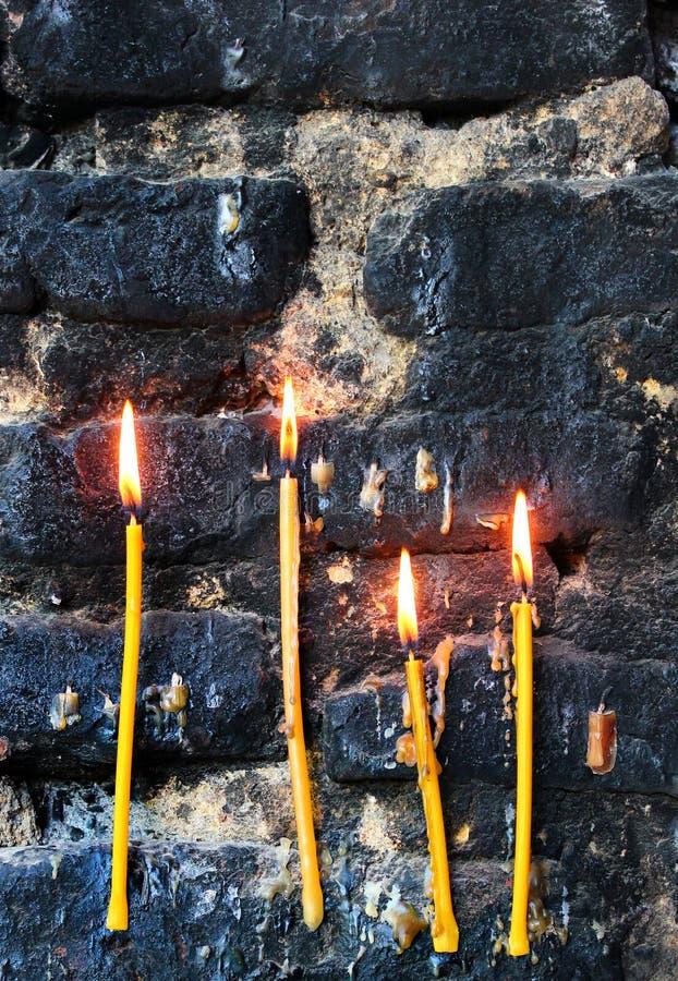 Τέσσερα καίγοντας κεριά στον παλαιό sooty μαυρισμένο τοίχο πετρών στοκ εικόνα