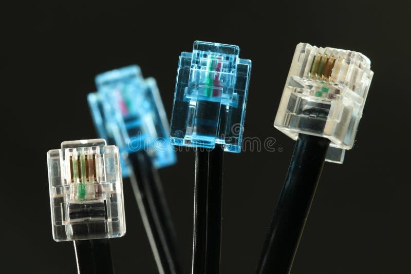 Τέσσερα καλώδια δικτύων με τον μπλε και άσπρο συνδετήρα rj στο Μαύρο στοκ εικόνες