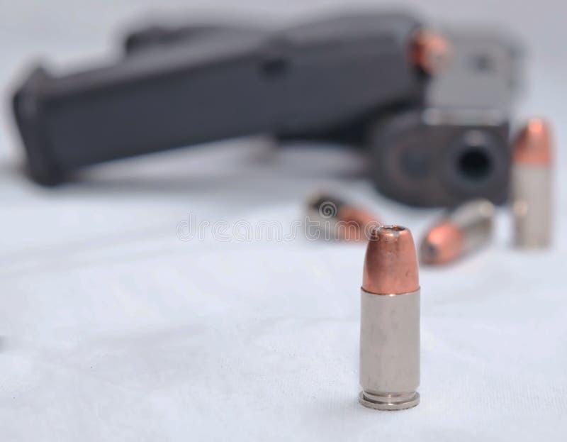 Τέσσερα κοίλο σημείο 9mm σφαίρες με ένα μαύρο πιστόλι στοκ φωτογραφίες με δικαίωμα ελεύθερης χρήσης