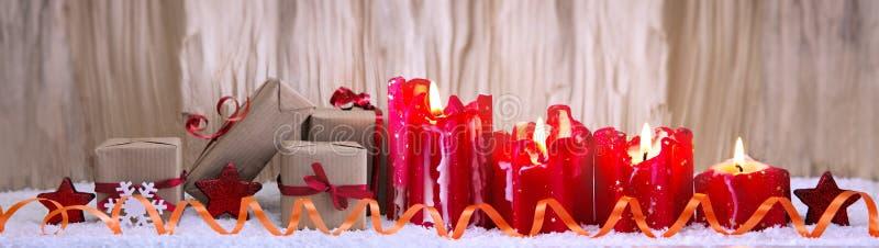 Τέσσερα κόκκινα καίγοντας κεριά για τα δώρα εμφάνισης και Χριστουγέννων στοκ φωτογραφίες
