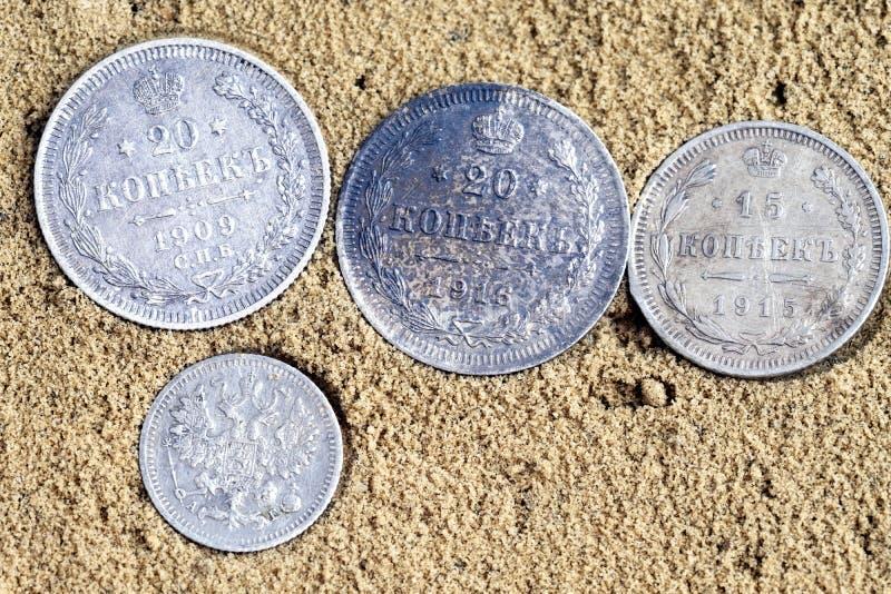 Τέσσερα νομίσματα στην άμμο, παλαιά ασημένια νομίσματα της Ρωσίας του δέκατου όγδοου αιώνα στοκ εικόνα