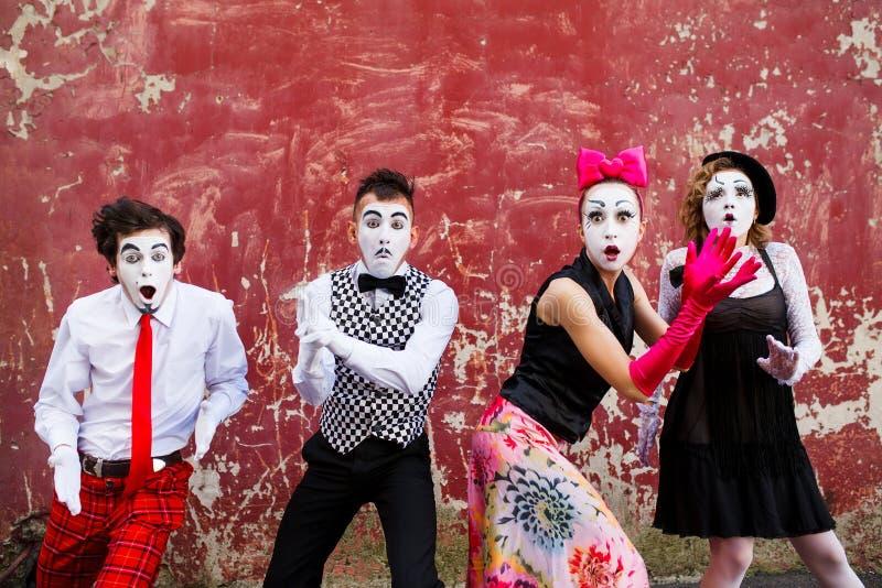 Τέσσερα οπλισμένη mimes στάση σε έναν κόκκινο τοίχο στοκ εικόνα