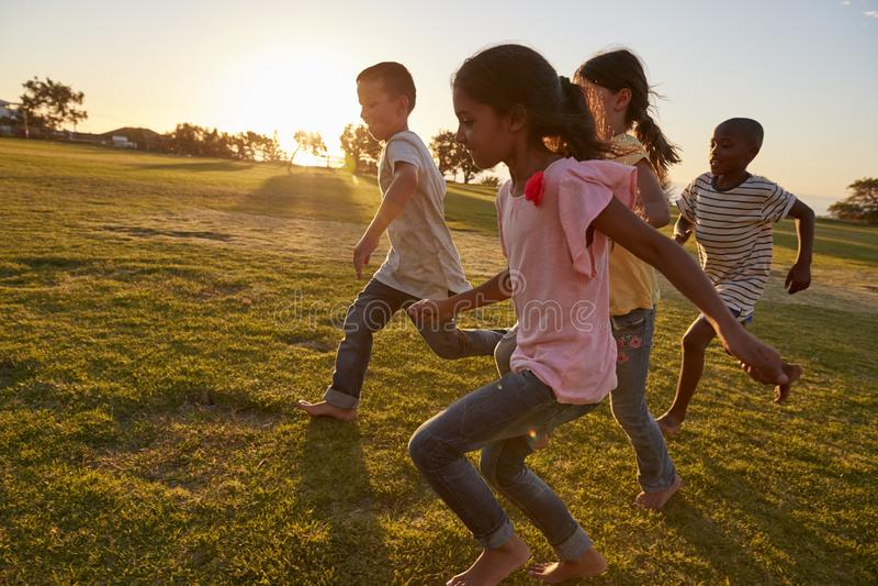 Τέσσερα παιδιά που τρέχουν χωρίς παπούτσια σε ένα πάρκο στοκ φωτογραφίες