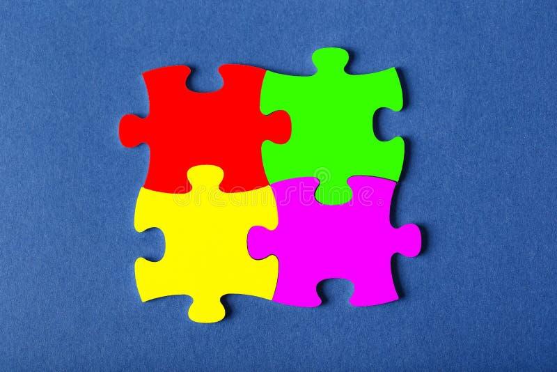 Τέσσερα στερέωσαν τους γρίφους των διαφορετικών χρωμάτων στο μπλε υπόβαθρο στοκ φωτογραφία