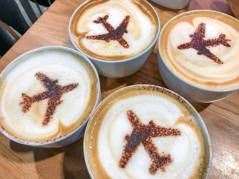 Τέσσερα φλιτζάνια του καφέ με τις σκιαγραφίες αεροπλάνων διακοπές διακοπών στοκ εικόνες