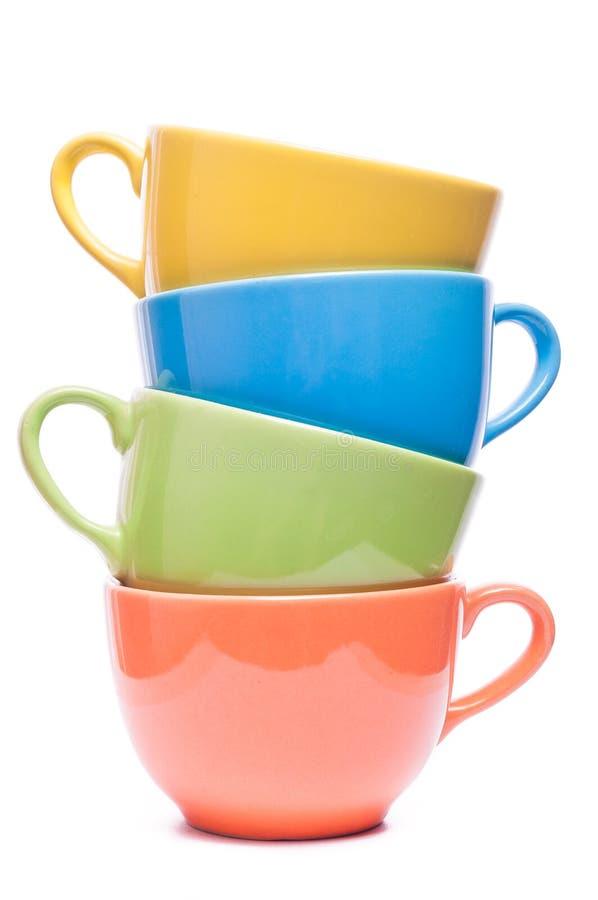 Τέσσερα φλυτζάνια που συσσωρεύονται χρωματισμένες κούπες Ζωηρόχρωμη εικόνα με το επιτραπέζιο σκεύος στοκ φωτογραφία με δικαίωμα ελεύθερης χρήσης