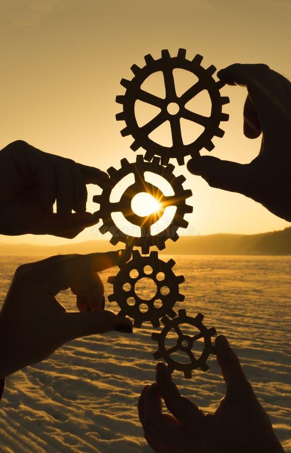 Τέσσερα χέρια κρατούν τα εργαλεία ενάντια στο ηλιοβασίλεμα στοκ φωτογραφία με δικαίωμα ελεύθερης χρήσης