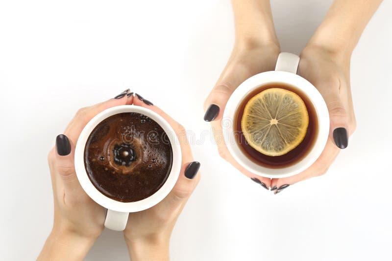 Τέσσερα χέρια με τα φλυτζάνια του τσαγιού και του καφέ στο άσπρο υπόβαθρο στοκ φωτογραφία