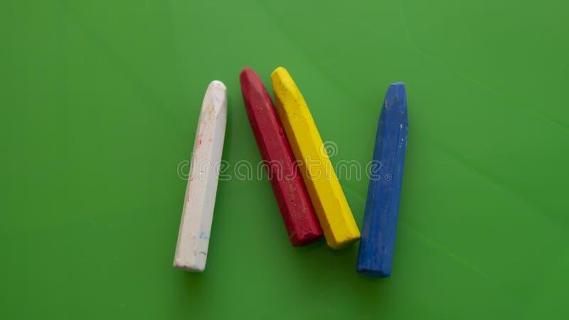 Τέσσερα χρωματισμένα μολύβια κεριών βρίσκονται στον πίνακα των πράσινων παιδιών στοκ φωτογραφία με δικαίωμα ελεύθερης χρήσης
