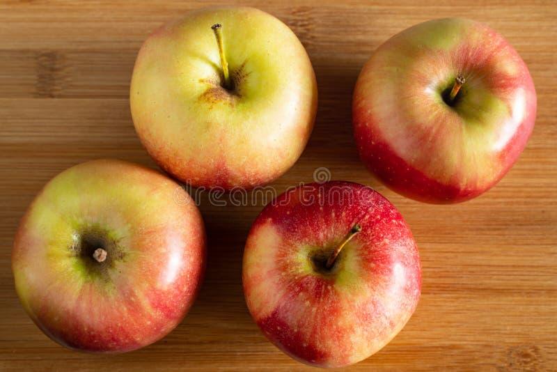 τέσσερα όμορφα κόκκινα κίτρινα μήλα που βρίσκονται σε ένα ξύλινο υπόβαθρο στοκ φωτογραφίες
