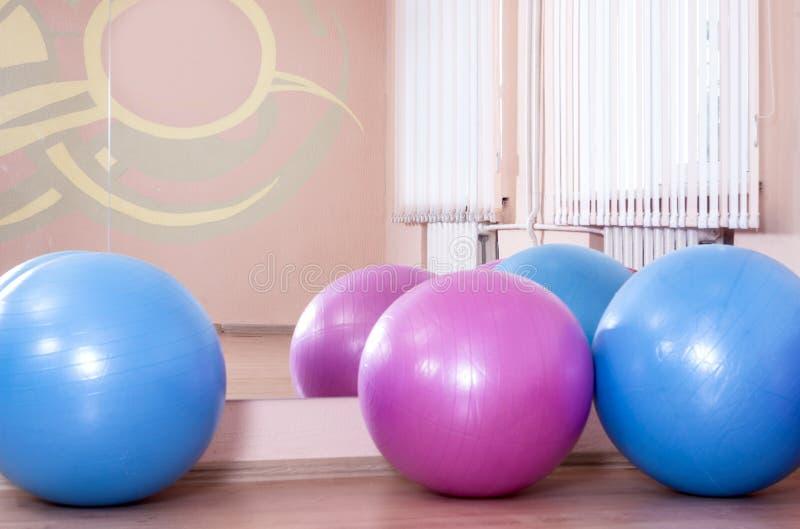 Τέσσερα Fitballs στο πάτωμα στο κέντρο αθλητικής ικανότητας στο εσωτερικό στοκ εικόνα