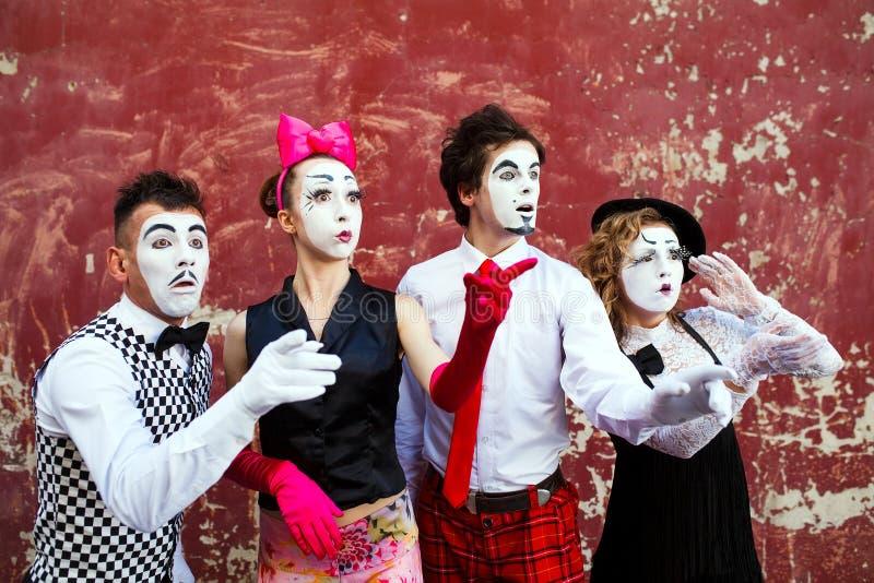 Τέσσερα mimes που κοιτάζουν κατά μέρος στο υπόβαθρο ενός κόκκινου τοίχου στοκ φωτογραφία με δικαίωμα ελεύθερης χρήσης