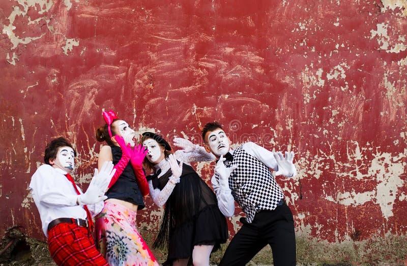 Τέσσερα mimes που στέκονται στο δέο στο υπόβαθρο ενός κόκκινου τοίχου στοκ φωτογραφία