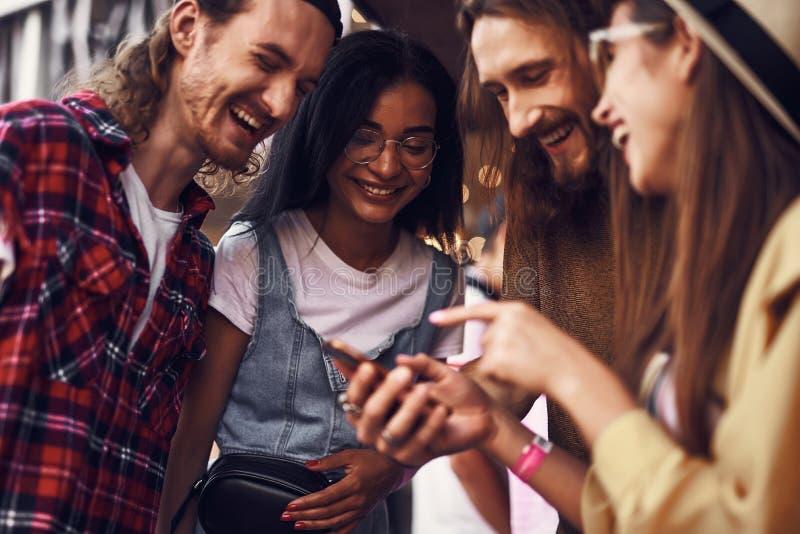 Τέσσερις άνθρωποι που γελούν προσέχοντας το αστείο βίντεο από κοινού στοκ εικόνα