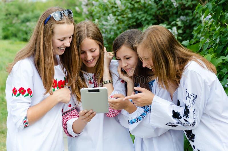 Τέσσερις αρκετά ευτυχείς φίλοι κοριτσιών εφήβων και υπολογιστής ταμπλετών στοκ φωτογραφίες