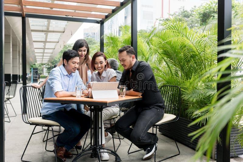 Τέσσερις ασιατικοί νέοι φίλοι που χαμογελούν προσέχοντας μαζί το αστείο ο στοκ εικόνες