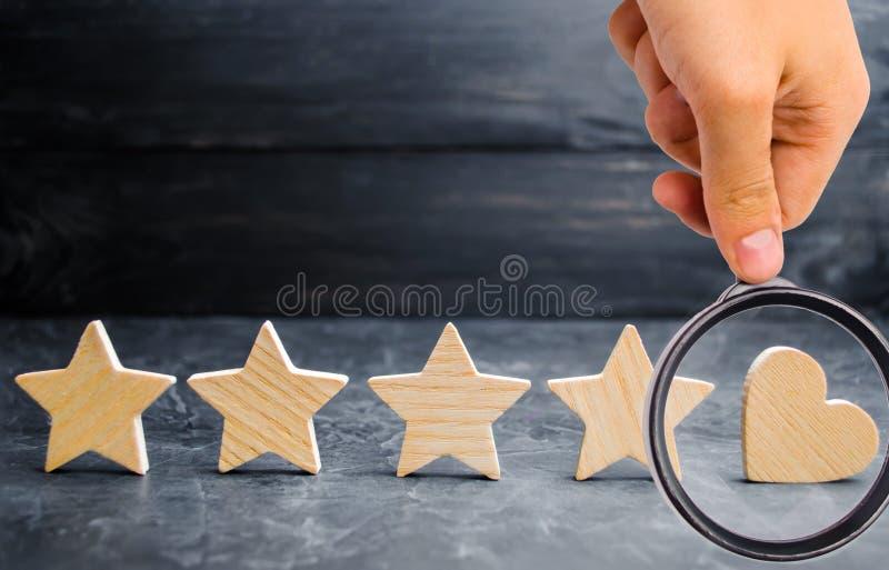 Τέσσερις αστέρια και καρδιά σε ένα μαύρο υπόβαθρο εκτίμηση πέντε αστεριών, τ στοκ εικόνες