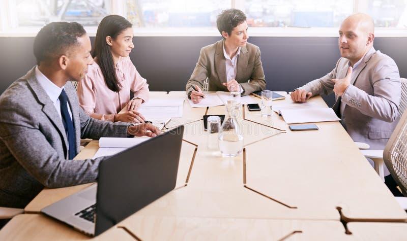 Τέσσερις επαγγελματικοί ανώτεροι υπάλληλοι που διευθύνουν μια επιχειρησιακή συνεδρίαση ξημερωμάτων στοκ φωτογραφίες