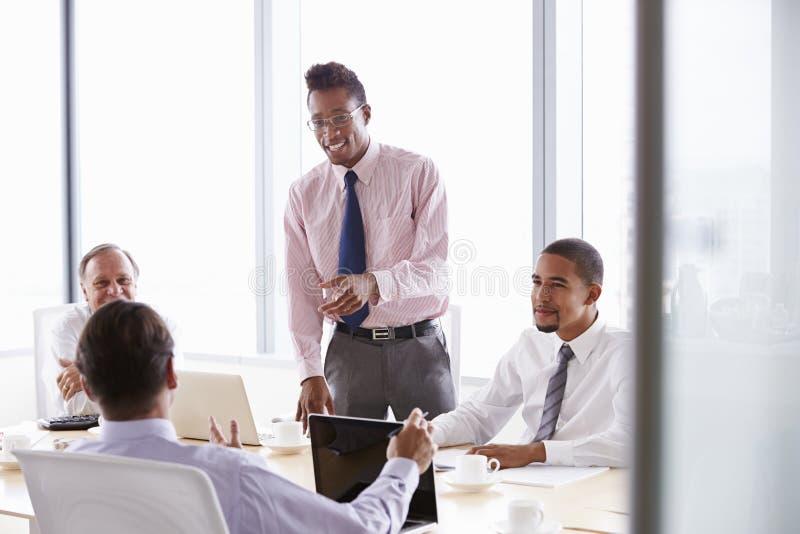 Τέσσερις επιχειρηματίες που διοργανώνουν τη συνεδρίαση γύρω από τον πίνακα αιθουσών συνεδριάσεων στοκ εικόνες