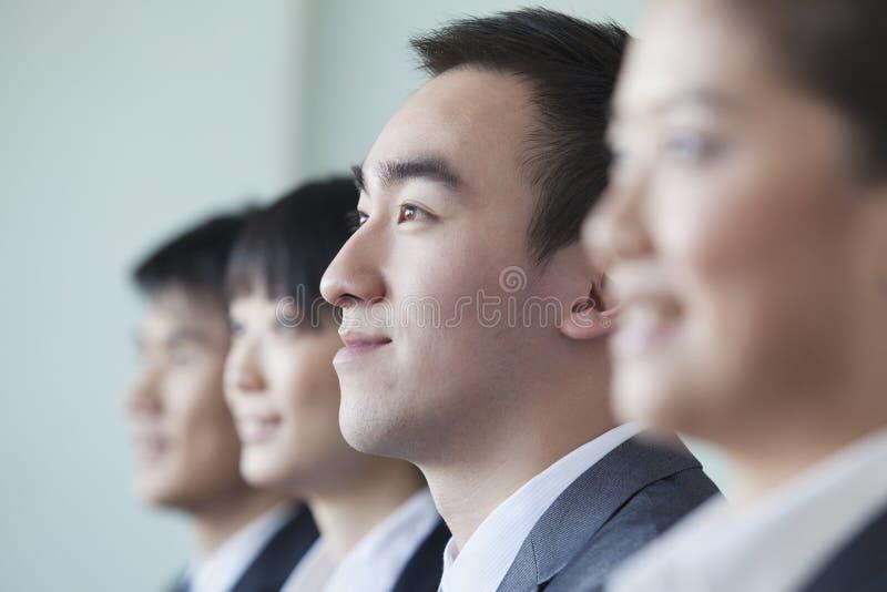 Τέσσερις επιχειρηματίες που κάθονται σε μια σειρά, πορτρέτο στοκ φωτογραφία με δικαίωμα ελεύθερης χρήσης