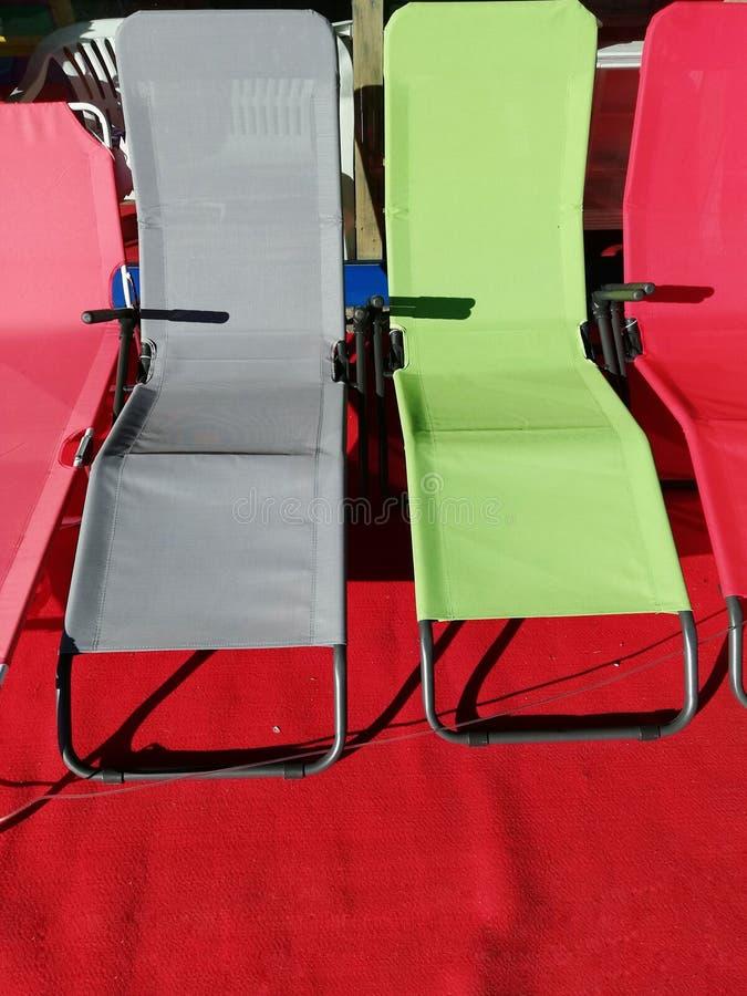 Τέσσερις καρέκλες παραλιών στα διαφορετικά χρώματα στο κόκκινο χαλί στοκ φωτογραφίες με δικαίωμα ελεύθερης χρήσης