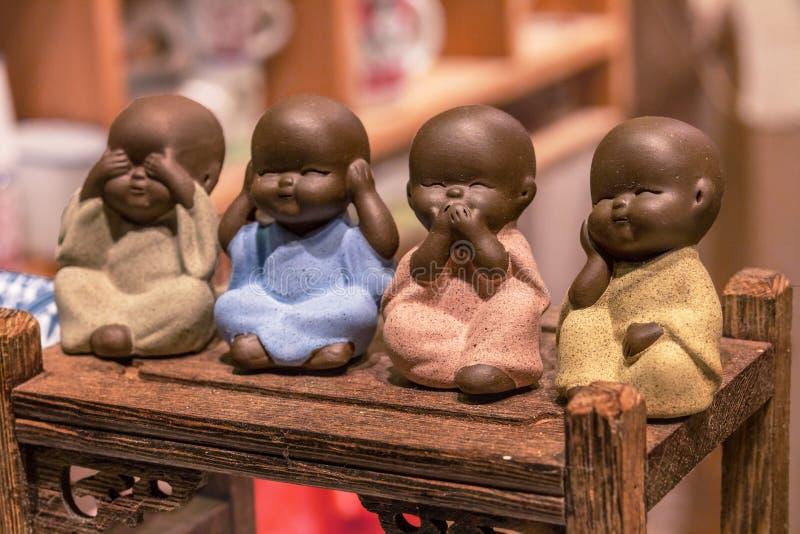 Τέσσερις μικροί μοναχοί, κλείνουν επάνω του χεριού που τα μικρά αγάλματα με την έννοια δεν βλέπουν κανένα κακό, δεν ακούνε κανένα στοκ εικόνα