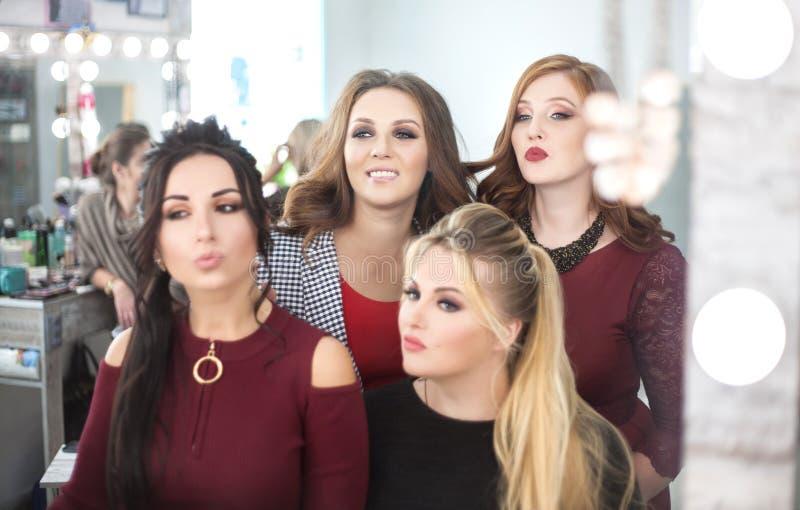 Τέσσερις νέες γυναίκες που κοιτάζουν στον καθρέφτη στο σαλόνι ομορφιάς στοκ εικόνα με δικαίωμα ελεύθερης χρήσης